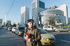 Retrato de la calle de un hombre joven con una mochila y una taza de café a disposición contra los coches y la arquitectura Un ho Foto de archivo