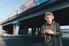 Retrato de la calle de un hombre joven en auriculares en la cabeza contra la calle Un hombre joven con música camina alrededor de Fotos de archivo libres de regalías