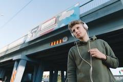 Retrato de la calle de un hombre joven que escucha la música en auriculares en el fondo del puente Imagenes de archivo