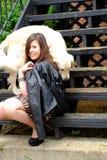 Retrato de la calle de una muchacha con un perro blanco imagen de archivo