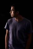 Retrato de la camiseta que lleva del hombre joven que se coloca con las manos en bolsillos Fotos de archivo