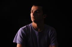 Retrato de la camiseta que lleva del hombre joven que se coloca con las manos en PC Imagen de archivo