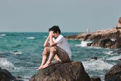 Retrato de la cara asiática joven triste sola de la cubierta del hombre con las manos y la sentada en la roca de la orilla de mar Fotos de archivo libres de regalías