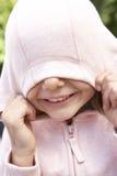 Retrato de la cara de ocultación de la muchacha en top con capucha rosado Imagenes de archivo