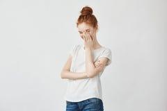 Retrato de la cara de risa de la mujer tímida hermosa joven del pelirrojo con las manos En el fondo blanco Copie el espacio Imagen de archivo libre de regalías