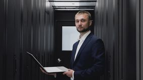 Retrato de la cara del ingeniero de las TIC con el ordenador portátil en el sitio del servidor del datacenter almacen de metraje de vídeo