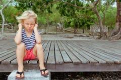 Retrato de la cara del niño caucásico enfadado, infeliz con los brazos cruzados imagenes de archivo