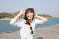 Retrato de la cara feliz de la mujer hermosa que se sienta en el mar de madera del puerto Imágenes de archivo libres de regalías