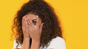 Retrato de la cara de ocultación asustada de la muchacha biracial en las manos, emociones del miedo, fobia almacen de metraje de vídeo