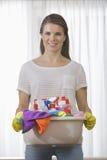Retrato de la cesta que lleva sonriente de la mujer de fuentes de limpieza en casa Fotos de archivo