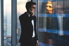 Retrato de la charla joven del hombre de negocios sobre el teléfono móvil mientras que haga una pausa su ventana de la oficina en imágenes de archivo libres de regalías