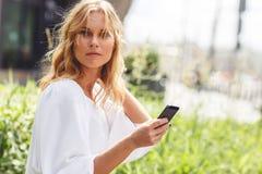 Retrato de la chica joven atractiva con el teléfono que mira la cámara Fotografía de archivo libre de regalías