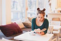 Retrato de la chica joven atractiva que goza de un buen café del libro y de la taza que se sienta en interior cómodo Imagenes de archivo
