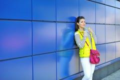 Retrato de la chica joven bastante alegre que se coloca cerca de una pared azul Imagenes de archivo