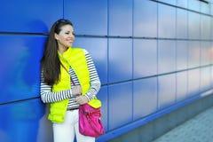 Retrato de la chica joven bastante alegre que se coloca cerca de una pared azul Fotografía de archivo libre de regalías