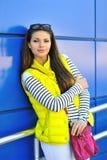 Retrato de la chica joven bastante alegre que se coloca cerca de una pared azul Imagen de archivo