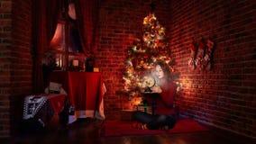 Retrato de la chica joven con el regalo cerca del árbol de navidad Fotografía de archivo