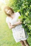 Retrato de la chica joven de Asia con el bolso que se coloca en parque Foto de archivo