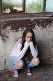 Retrato de la chica joven deprimida que se inclina en la pared del edificio arruinado Imagen de archivo libre de regalías