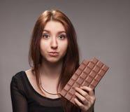Retrato de la chica joven desconcertada con el chocolate grande Imagenes de archivo