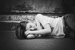Retrato de la chica joven durmiente en el asfalto Fotos de archivo libres de regalías