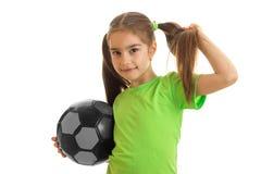 Retrato de la chica joven en camisa verde con el balón de fútbol en manos Fotos de archivo