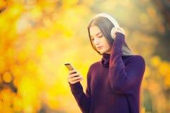 Retrato de la chica joven feliz con los auriculares y de la música que escucha del smartphone en parque del otoño Fotografía de archivo