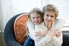 Retrato de la chica joven feliz que abraza a la abuela Foto de archivo libre de regalías