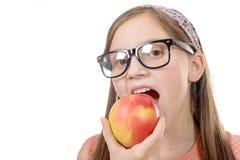 Retrato de la chica joven feliz que come una manzana sobre el backgro blanco Fotografía de archivo