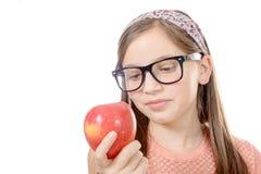 Retrato de la chica joven feliz que come una manzana sobre el backgrou blanco Foto de archivo
