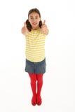 Retrato de la chica joven feliz que da los pulgares para arriba Imagen de archivo libre de regalías