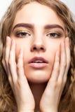 Retrato de la chica joven hermosa con las manos en la cara Foto de archivo libre de regalías