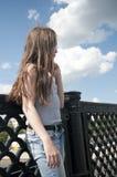 Retrato de la chica joven hermosa en el fondo del cielo azul del puente con el pelo que sopla en viento Imagen de archivo