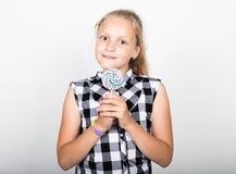 Retrato de la chica joven hermosa feliz con los candys dulces la chica joven bonita se vistió en una camisa de tela escocesa que  Imagen de archivo