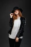 Retrato de la chica joven hermosa que lleva el sombrero de fieltro y el leat negros Imagen de archivo