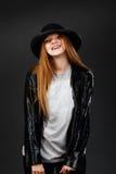 Retrato de la chica joven hermosa que lleva el sombrero de fieltro y el leat negros Imagenes de archivo