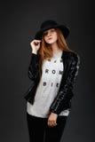 Retrato de la chica joven hermosa que lleva el sombrero de fieltro y el leat negros Fotografía de archivo