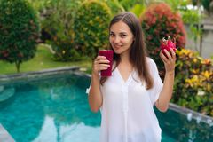Retrato de la chica joven hermosa que sostiene el vidrio de smoothie de la fruta del dragón y de fruta en sus manos cerca de pisc fotos de archivo