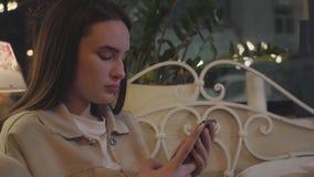 Retrato de la chica joven linda que manda un SMS en su teléfono celular que se sienta en la tabla en el restaurante El pedazo de  almacen de metraje de vídeo
