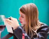 Retrato de la chica joven linda que pone el lápiz labial rojo Fotos de archivo