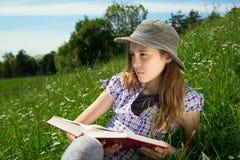 Retrato de la chica joven pensativa con el libro en sus manos que se sientan en la hierba en la ladera y que miran cuidadosamente Fotos de archivo