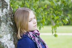 Retrato de la chica joven que coloca el árbol de abedul cercano Fotos de archivo