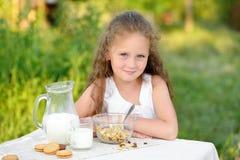 Retrato de la chica joven que come el desayuno y la leche de consumo al aire libre Cereal, forma de vida sana Fotografía de archivo