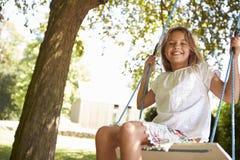 Retrato de la chica joven que juega en el oscilación del árbol Fotografía de archivo libre de regalías