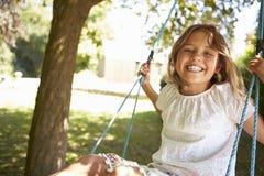 Retrato de la chica joven que juega en el oscilación del árbol Foto de archivo libre de regalías