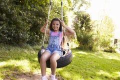 Retrato de la chica joven que juega en el oscilación del neumático en jardín Imagen de archivo