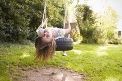 Retrato de la chica joven que juega en el oscilación del neumático en jardín Fotos de archivo
