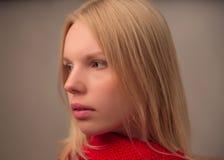 Retrato de la chica joven que lleva la bufanda roja en el fondo blanco Fotografía de archivo libre de regalías