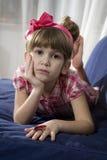Retrato de la chica joven que miente en el sofá Fotografía de archivo