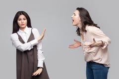 Retrato de la chica joven que mira la cámara y que muestra la parada o ignorar a otra muchacha que grita en ella conflicto entre  imagenes de archivo